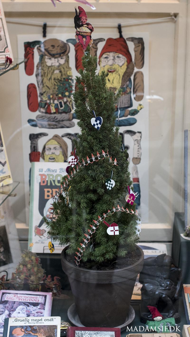 Flettede julehjerter og en nisse i toppen pryder dette lillebitte træ. I baggrunden ses et klippeark, der blev populære i slutningen af 1800-tallet. Taget gennem ruden hos boghandleren i Den Gamle By.